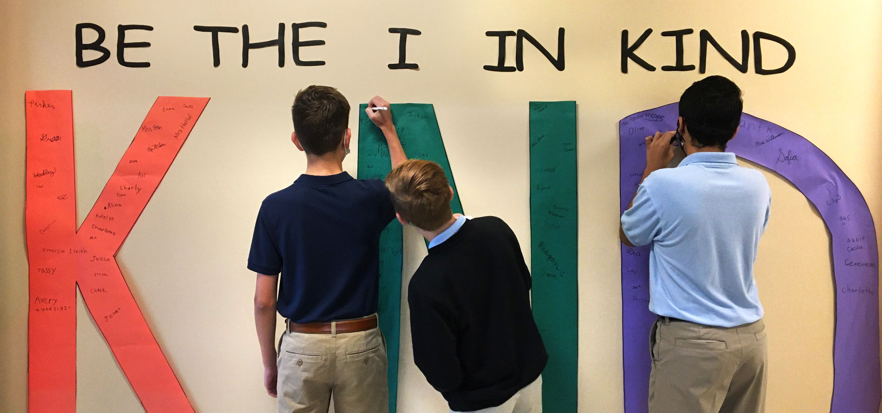 3 eight grade students standing in front of wall display that reads Be the I in KIND.