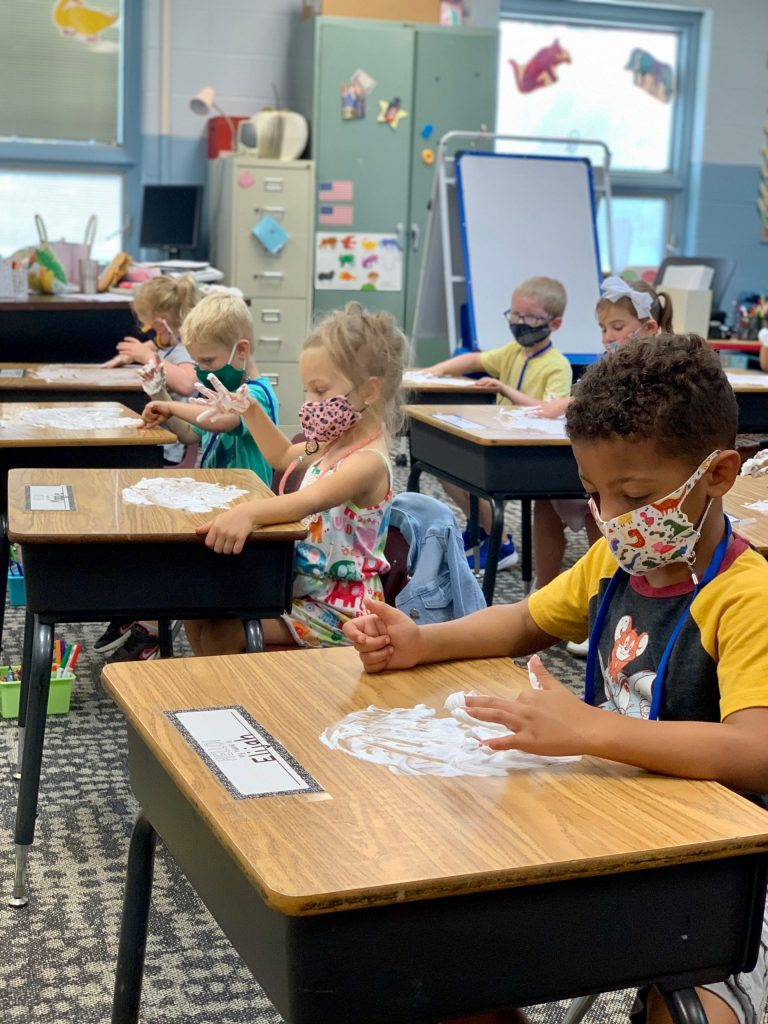 Preschool boy using finger to write in a pile of shaving cream on his desk. More students doing the same in the background.